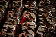 Young graduates wearing rented gowns and mortarboards applaud a speech in the central hall of their university during their graduation ceremony, on 13th July 2017, at the University of York, England.