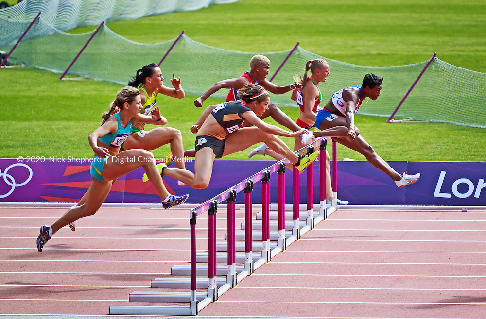 Reina-Flor OKORI, leading the pack of runners behind Sally Pearson in the 2012 Olympic heat of the womens 100m hurdles at the Olympic Park in Stratford, London, UK. This is the moment Ekaterina Poplavskaya of Belarus, running around the hurdle, ended her Olympic dream through disqualification.