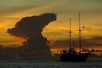 Traditional Indonesian vessel at anchor of Pisang Islands with anvil shaped thunderhead cloud at sunset..Pisang Islands, W of Fak Fak Peninsula, Ceram Sea..Alfred Russel Wallace sailed through this very area in traditional boats.