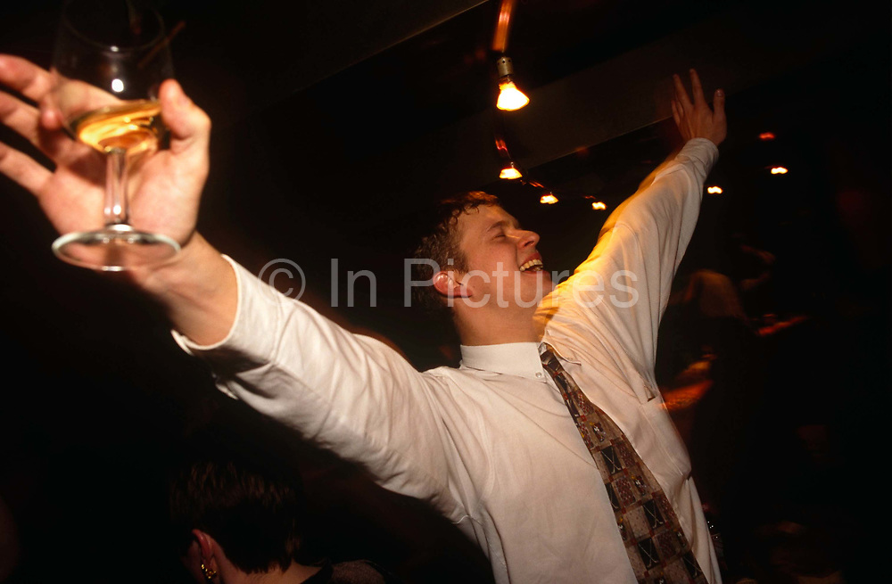 A young man in his twenties parties in the evening at a Coates Wine Bar on London Wall in the heart of the City of London, England. Holding a small glass containing a shot of alcohol, he sings at the top of his voice during a Karaoke night. He wears a shirt and tie so probably works in an office. Without a care in the world he has closed his eyes to enjoy the moment of elation and alcohol. It's dark in the bar with few lights in the background but spotlights have little effect to brighten up the scene.