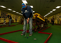 Kyle Heney makes a steady putt in the mini golf game during the NH Humane Society Indoor Triathlon at Funspot on Saturday.   (Karen Bobotas/for the Laconia Daily Sun)