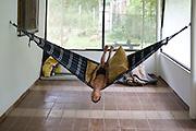 A boy swings on a hammock in Pylons, Cubatão