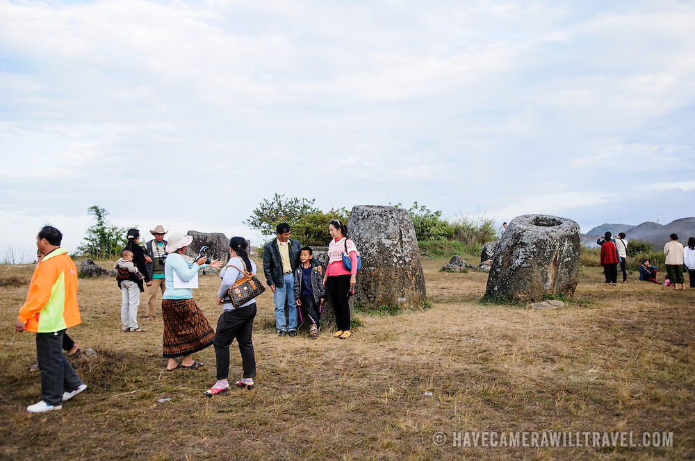 A family poses for photos amongst the stone jars at Site 1 of the Plain of Jars in north-central Laos. Much remains unknown about the age and purpose of the thousands of stone jars clustered in the region. Most accounts date them to at least a couple of thousand years ago and theories have been put forward that they were used in burial rituals.