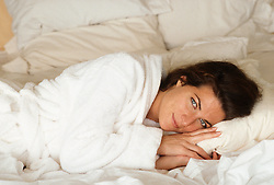 woman in a white  bathrobe resting in bed