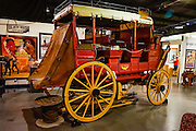 """This 3-seat, 9-passenger red Wells Fargo Express coach carried US Mail and passengers on rough roads in the West. This Celerity wagon was made by John Butterfield between 1858-1861 and much later converted with disc brakes for parade use. It was designed with half the weight of standard coaches and a lower floor for better shock absorption on rough, sandy, and steep trails. The name """"Celerity"""" comes from the Latin root celer meaning swift. Celerity wagons covered 70 to 120 miles per day (averaging 4 to 7 miles per hour), making stops about every 20 miles. The Butterfield Overland Mail Trail was a stagecoach route operating from 1857 to 1861, carrying US mail starting from Memphis, Tennessee and St. Louis (Tipton), Missouri. The service routes converged at Fort Smith, Arkansas and passed through Indian Territory, New Mexico, and southern Arizona, ending in San Francisco. This particular wagon served the California towns of Stockton, Jamestown, Sonora, and Columbia. To discourage theft, gold and silver was not allowed on board; and the Butterfield Stage system was only attacked once, by Apaches. Fans of movies and television shouldn't miss the Museum of Western Film History, 701 S. Main Street, Lone Pine, California, 93545, USA. Web site: www.lonepinefilmhistorymuseum.org"""