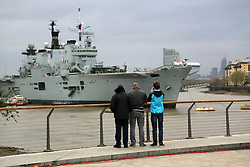© Licensed to London News Pictures. 08/05/2013. London, UK. Spectators watch HMS Illustrious. Royal Navy sea king helicopter  lands on HMS Illustrious. A Royal Navy flypast, including a Sea King and Merlin, over Greenwich as part of events to mark the 70th anniversary of the Battle of the Atlantic. The fly past was shown live on BBC1 on the One Show.. Photo credit : Rob Powell/LNP