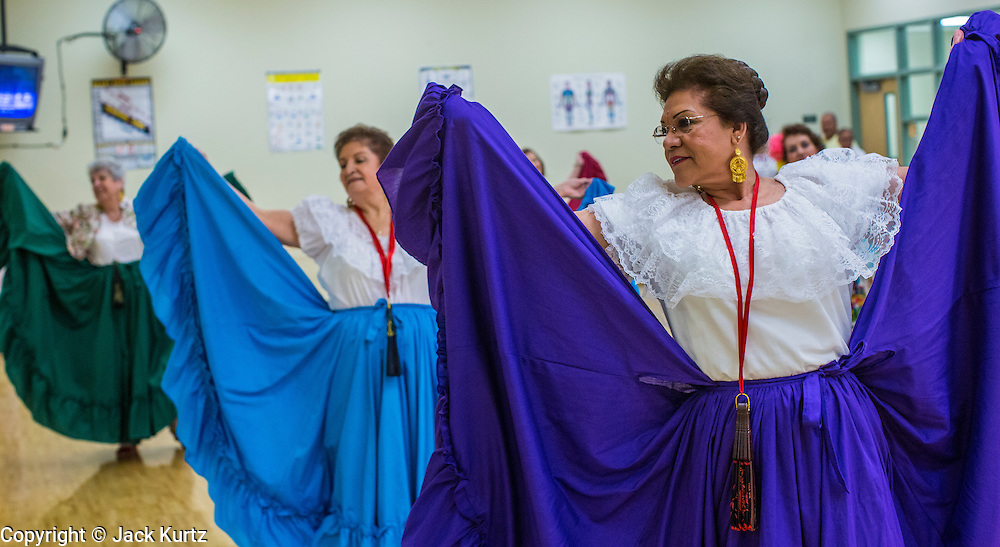 27 JUNE 2012 - GLENDALE, AZ:  MARGIE MAY, 65 years old, right, and other members of the Senior Fiesta Dancers,  dance during rehearsal for the Senior Fiesta Dancers at the Glendale Adult Center, in Glendale, AZ, a suburb of Phoenix. Dancing as a part of workout regimen is not unusual, but the Senior Fiesta Dancers use Mexican style folklorico dances for their workouts. The Senior Fiesta Dancers have been performing together for 15 years. They get together every week for rehearsals and perform at nursing homes and retirement centers in the Phoenix area once a month or so. Their energetic Mexican folklorico dances keep them limber and provide a cardio workout.   PHOTO BY JACK KURTZ