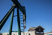 Oil well and pumpjacks next to a McDonald's in the City of Signal Hill. Once a massive oil producing area, oil wells are still mixed in its now residential neighborhoods. Los Angeles Coutny, California, USA