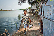 Apr. 3, 2010 - KHUN SAMUTCHINE, THAILAND:  A woman walks home from after shopping at a small convenience stand in Khun Samutchine. Rising sea levels brought about by global climate change threaten the future of Khun Samutchine, a tiny fishing village about 90 minutes from Bangkok on the Gulf of Siam. The coastline advances inland here by about 20 metres (65 feet) per year causing families to move and threatening the viability of the village. The only structure in the village that hasn't moved, their Buddhist temple, is completely surrounded by water and more than 2 kilometers from the village. The temple and the village have asked the Thai government and several NGOs for help, but the only help so far is a narrow concrete causeway the government is building that will allow people to walk into the temple from a boat landing two miles away.  The walk to the village from a closer boat landing is shorter, but over an unimproved mud flat that is nearly impassible in the rainy season. PHOTO BY JACK KURTZ