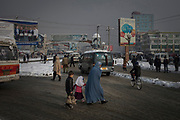 A woman with her children crosses a busy street in the capital Kabul, February 4, 2020. Kabul has become one of the most polluted cities in the world. For several months per year, especially in the winter time, the city gets blanketed by a toxic haze of particulate matter. Small and often invisible toxic particles that threaten the health of its six million residents.
