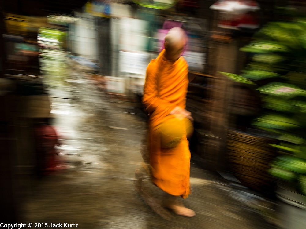 28 SEPTEMBER 2015 - BANGKOK, THAILAND:  A Buddhist monks walks through the neighborhood at Wat Kalayanamit. Fifty-four homes around Wat Kalayanamit, a historic Buddhist temple on the Chao Phraya River in the Thonburi section of Bangkok, are being razed and the residents evicted to make way for new development at the temple. The abbot of the temple said he was evicting the residents, who have lived on the temple grounds for generations, because their homes are unsafe and because he wants to improve the temple grounds. The evictions are a part of a Bangkok trend, especially along the Chao Phraya River and BTS light rail lines. Low income people are being evicted from their long time homes to make way for urban renewal.   PHOTO BY JACK KURTZ