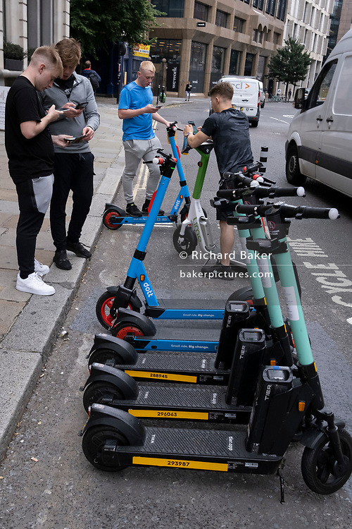 Young men use their phones to rent Dott and Lime eScooters, all standing within a special area for licensed and therefore legal rental eScooters, in the City of London, on 12th July 2021, in London, England.