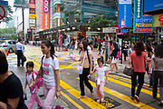 Pedestrians cross a busy road crossing in the Causeway Bay area of Hong Kong, China. Causeway Bay is a thronging shopping district, with a slightly less western influence than nearby Central district.