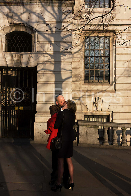 A mature romantic couple cuddle in a London street. As late sun throws the shadows of large London Plane trees across the walls of the South African Embassy in the capital's Trafalgar Square, the man and woman seem oblivious to all else about them except their own private space. The lady's head is angled to one side before another smooch, her long legs and smart clothes evident of an evening date in the city. The classic kiss on a street corner.