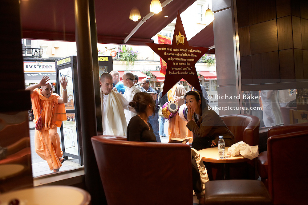 Two customers in a Pret a Manger sandwich chain try to ignore Hari Krishna devotees who chant through the window, London.