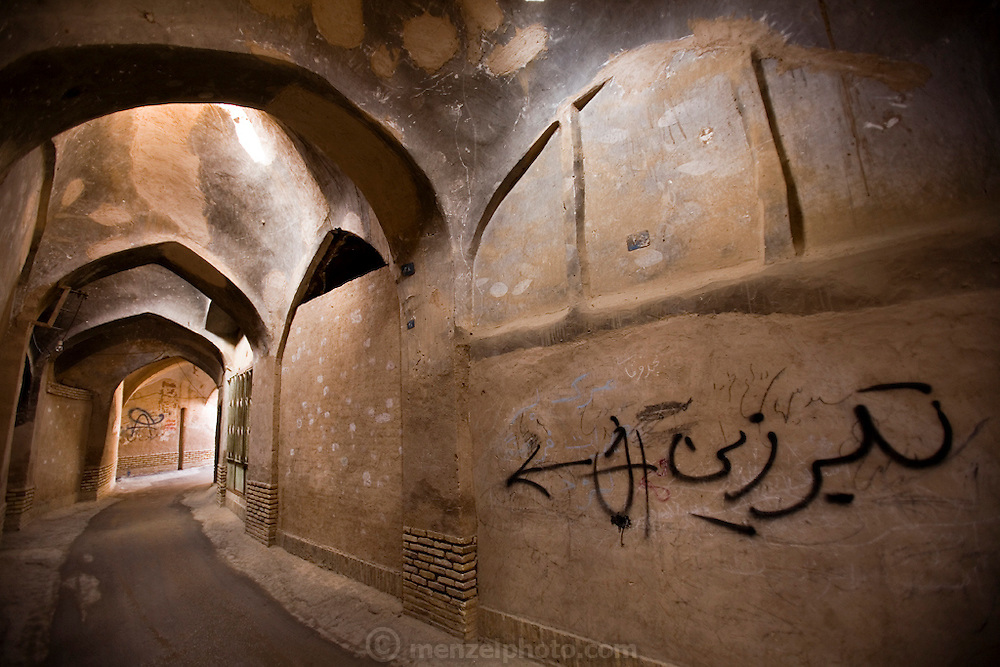 """Part of a labyrinth of covered streets and alleys that wind through the ancient mud brick city of Yazd, Iran. The grafitti on the wall on the right says """"battle-axe""""."""