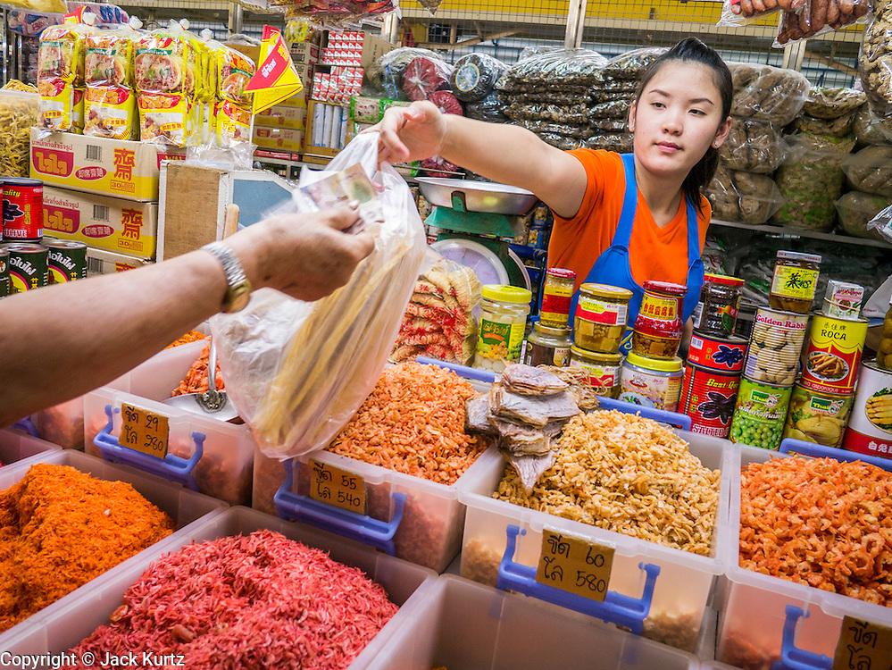 12 OCTOBER 2012 - NAKHON PATHOM, NAKHON PATHOM, THAILAND: A market vendor in the Nakhon Pathom market accepts payment for dried shrimp from a customer.   PHOTO BY JACK KURTZ