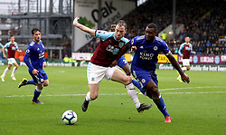 Burnley's Ashley Barnes (left) and Leicester City's Wes Morgan (right) battle for the ball during the Premier League match at Turf Moor, Burnley.