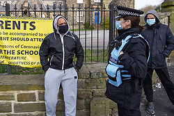 © Licensed to London News Pictures. 26/03/2021. Batley, UK. Police watch as people gather outside Batley Grammar School, West Yorkshire, after a teacher showed cartoons of the Prophet Mohammed in a religious studies lesson. The teacher has been suspended from his role. Photo credit:  Ioannis Alexopoulos/LNP