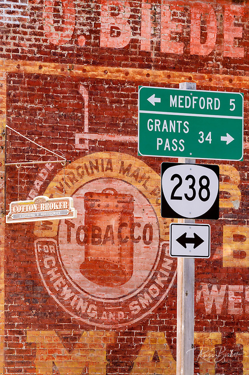 Road sign and historic advertisement on red brick building, Jacksonville, Oregon USA