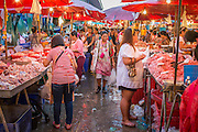 "03 OCTOBER 2012 - BANGKOK, THAILAND:    Shoppers in Khlong Toey Market in Bangkok. Khlong Toey (also called Khlong Toei) Market is one of the largest ""wet markets"" in Thailand. Thousands of people shop in the sprawling market for fresh fruits and vegetables as well meat, fish and poultry every day.      PHOTO BY JACK KURTZ"