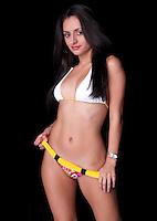 Young hispanic woman posing in bikini with black background.