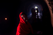 """10th December 2015, New Delhi, India. A woman in the ruins of Feroz Shah Kotla in New Delhi, India on the 10th December 2015<br /> <br /> PHOTOGRAPH BY AND COPYRIGHT OF SIMON DE TREY-WHITE a photographer in delhi<br /> + 91 98103 99809. Email: simon@simondetreywhite.com<br /> <br /> People have been coming to Firoz Shah Kotla to pray to and leave written notes and offerings for Djinns in the hopes of getting wishes granted since the late 1970's. Jinn, jann or djinn are supernatural creatures in Islamic mythology as well as pre-Islamic Arabian mythology. They are mentioned frequently in the Quran  and other Islamic texts and inhabit an unseen world called Djinnestan. In Islamic theology jinn are said to be creatures with free will, made from smokeless fire by Allah as humans were made of clay, among other things. According to the Quran, jinn have free will, and Iblīs abused this freedom in front of Allah by refusing to bow to Adam when Allah ordered angels and jinn to do so. For disobeying Allah, Iblīs was expelled from Paradise and called """"Shayṭān"""" (Satan).They are usually invisible to humans, but humans do appear clearly to jinn, as they can possess them. Like humans, jinn will also be judged on the Day of Judgment and will be sent to Paradise or Hell according to their deeds. Feroz Shah Tughlaq (r. 1351–88), the Sultan of Delhi, established the fortified city of Ferozabad in 1354, as the new capital of the Delhi Sultanate, and included in it the site of the present Feroz Shah Kotla. Kotla literally means fortress or citadel."""