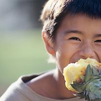 Boy resident of Lanai eating pineapple.