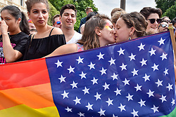 © Licensed to London News Pictures. 08/07/2017. London, UK.  Girls kiss whilst carrying a rainbow inspired USA flag.  Tens of thousands of visitors, many wearing eye-catching costumes, gather to watch and take part in the annual Pride in London Parade, the largest celebration of the LGBT+ community in the UK.   Photo credit : Stephen Chung/LNP