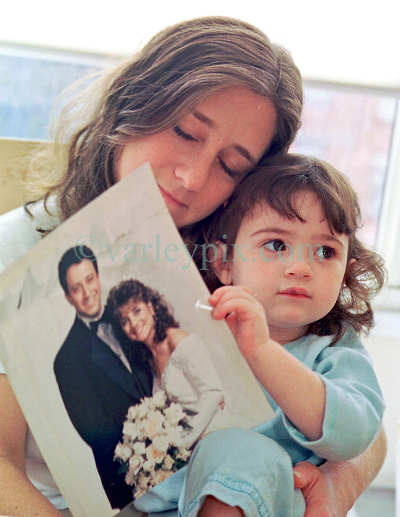 15 September 2001. New York, New York - USA.<br /> Post 9/11 World Trade Center attack.<br /> Jill Gartenberg and her 2 year old daughter Nicole at their apartment with a photo of her late husband Jim who made many calls home from the World Trade Center before the towers collapsed killing him and over 2,000 other victims of Al-Qaeda's coordinated attacks on the Twin Towers.<br /> Photo exclusive©; Charlie Varley/varleypix.com
