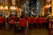 Wearing red uniforms, a military band takes a breather between musical evening to help with the Poppy Appeal, in Leadenhall Market in the Square Mile, the heart of the capitals historical financial district, on 2nd October 2017, in the City of London, England.
