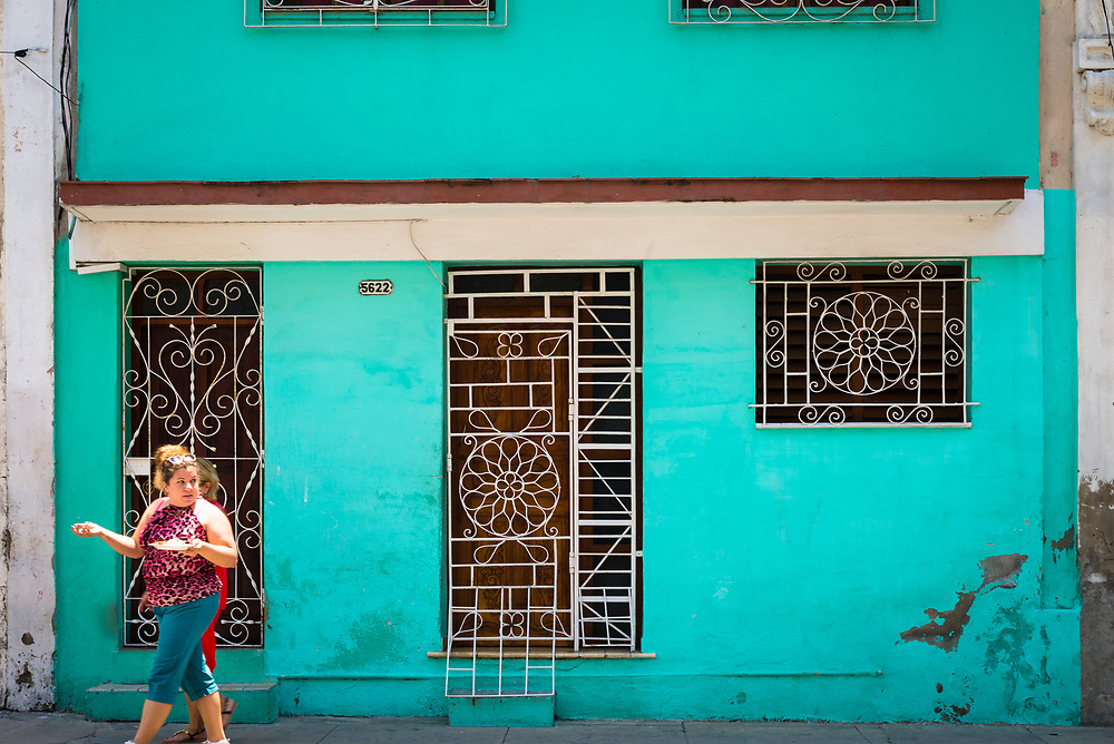 Woman walking past a colourful facade in Cienfuegos