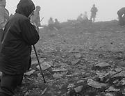 A pilgrim kneels in prayer at the summit.