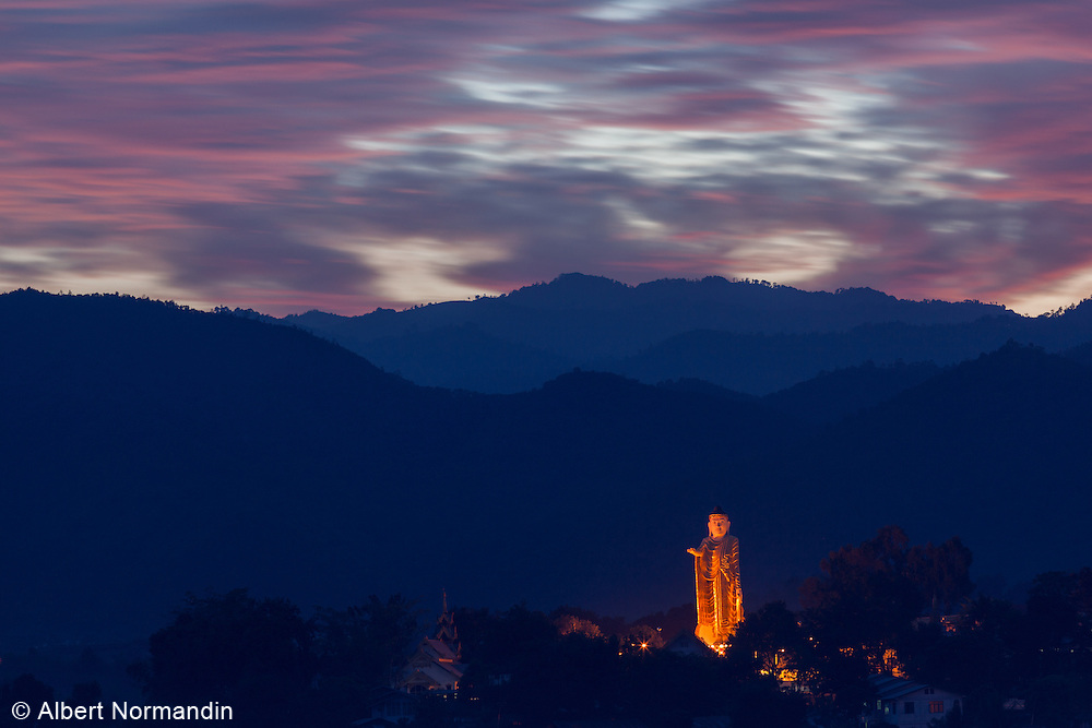 Yat Thaw Mu, Standing Buddha statue with lights, mountains, colourful sky and clouds. Kyaing Tong