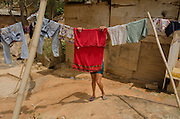 A woman hangs the cleaned clothes outside her makeshift low quality plywood shack in Esperança Occupancy, Isidoro area.