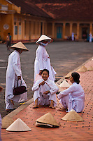 Women Cao Dai worshippers gather and chat around the Holy See in Tay Ninh prior to the dawn service.