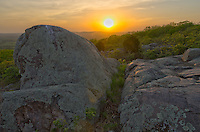 The sun sets in between two boulders. The boulders are part of a glade, which is a rocky, treeless area commonly found in the Ozark Mountains of Missouri.<br />