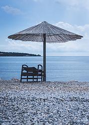 THEMENBILD - eine leere Strandliege und ein Sonnenschirm aus Schildrohr auf einem Kieselstrand, aufgenommen am 03. Juli 2020 in Novigrad, Kroatien // an empty beach chair and a reed umbrella on a pebble beach, in Novigrad, Croatia on 2020/07/03. EXPA Pictures © 2020, PhotoCredit: EXPA/ Stefanie Oberhauser