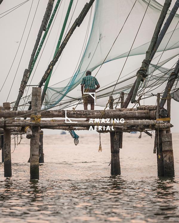 Kochi, India - 05 April 2019: view of fishermen working at sunset on the beach near the Chinese nest, Kochi, Kerala, India.