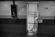 An inmate walks into the shower cell in the area reserved for inmates serving time.  The towels put up by inmates to attempt at some privace.  The telephone to the left can be used by any inmate but is accessed using a PIN number that needs to be set up by a family member with preparid plan.   The Bristol County Jail & House of Correction located on Ash Street in New Bedford, Massachusetts was started in 1829, and is the oldest running jail in the United States.   The Ash street jail, as it is known, has been a controversial facility since it opened.  It is believed to be the site of the last pubic hanging in Massachusetts sometime in the 1890's.  Two big riots broke out in the 90's (1993, 1998) and since then the facility has been modified to alleviate some of the crowded conditions that resulted in the riots.