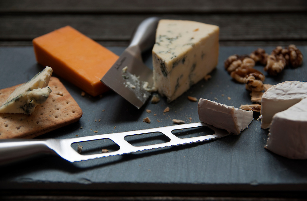 A selection of British Cheeses displayed on a slate board.