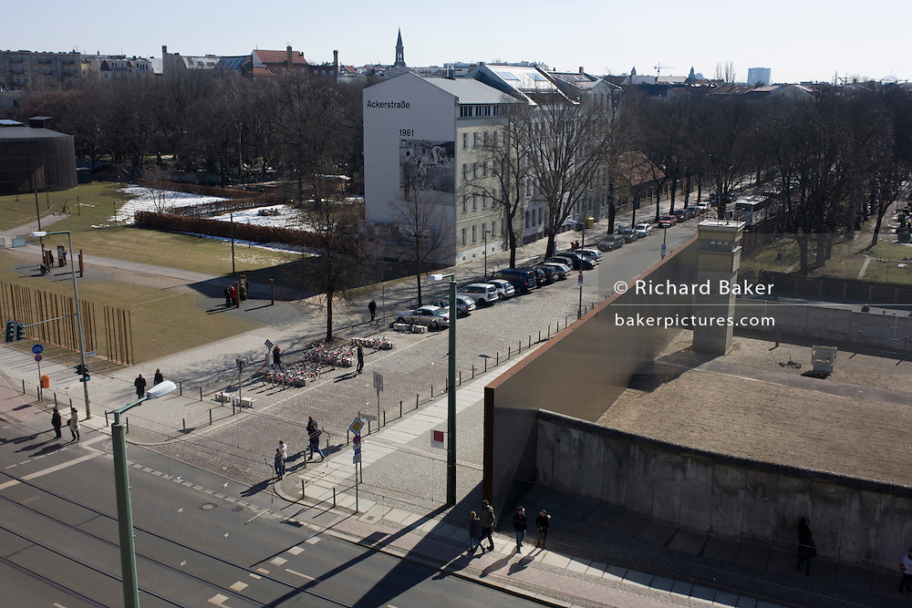"""Aerial landscape of Bernauer Strasse, showing a section of preserved Berlin wall where East Germans were killed while trying to cross the former border between Communist East and West Berlin during the Cold War. The Berlin Wall was a barrier constructed by the German Democratic Republic (GDR, East Germany) starting on 13 August 1961, that completely cut off (by land) West Berlin from surrounding East Germany and from East Berlin. The Eastern Bloc claimed that the wall was erected to protect its population from fascist elements conspiring to prevent the """"will of the people"""" in building a socialist state in East Germany. In practice, the Wall served to prevent the massive emigration and defection that marked Germany and the communist Eastern Bloc during the post-World War II period."""