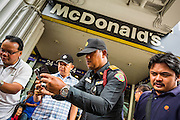 31 MAY 2014 - BANGKOK, THAILAND: A Thai policeman leans in to photograph a group of women who started singing Thai protest, pro-democracy and folk songs in a spontaneous protest against the coup front of a McDonald's in Bangkok. Some McDonald's restaurants in Thailand have become gathering places for anti-coup protestors. The restaurant chain has taken out ads trying to discourage people from protesting in and around the restaurants and put up signs asking people not to protest in the restaurant. Bangkok was mostly quiet Saturday. There were only a few isolated protests against the coup and military government.    PHOTO BY JACK KURTZ