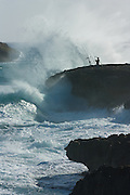A fisherman braves giant winter surf batters Oahu's shore at Laie Point, Hawaii