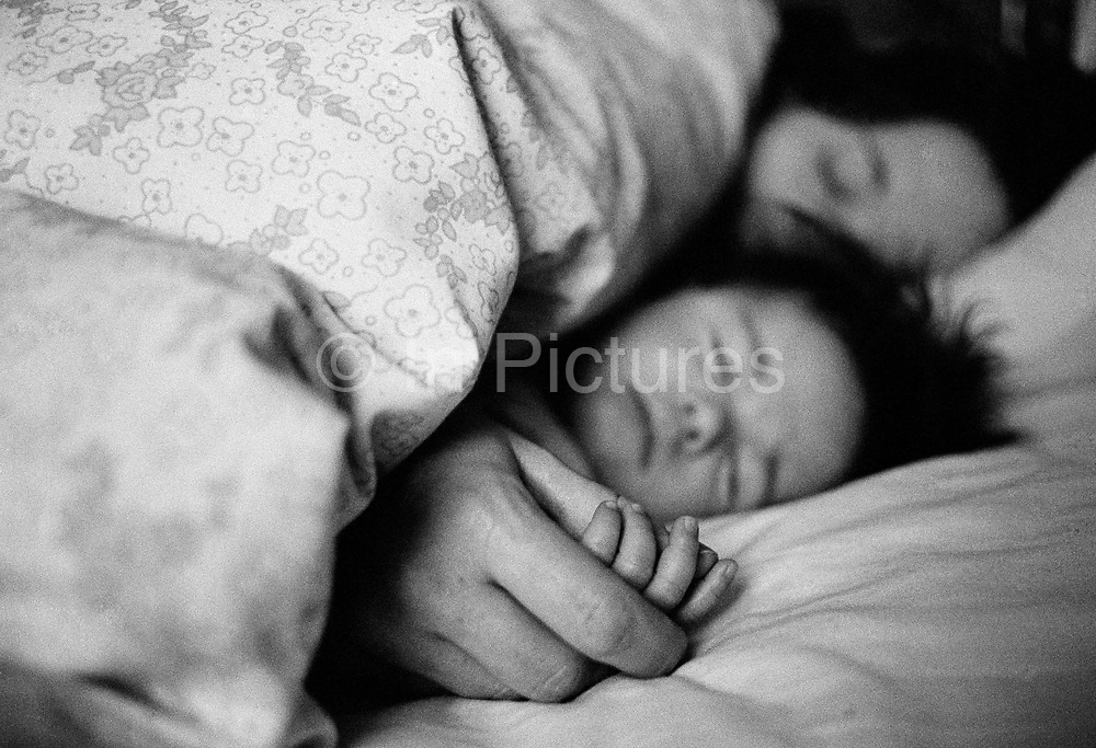 """""""Anywhere between 3-5am."""" A mother has brought her three and a half month-old infant into bed and comforts her new baby back to sleep in bed by holding her hand at dawn, after a broken night's rest. We see large adult's fingers encircling the tiny digits of the baby girl who is mercifully sound asleep again, instinctively aware of love and trust. It is a picture of protective parenthood, of a close bond between mother and child in a safe, cosy, warm and idyllic place within the loving family home. This is from a documentary series of pictures about the first year of the photographer's first child Ella. Accompanied by personal reflections and references from various nursery rhymes, this work describes his wife Lynda's journey from expectant to actual motherhood and for Ella - from new-born to one year-old."""