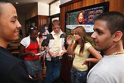 Teenagers in cinema looking at programmes.