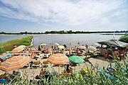 Nederland, Nijmegen, 30-6-2019Door het aanhoudende warme en droge weer zoeken veel mensen verkoeling aan het water zoals hier  bij rivierstrand met terras De Sprok in Lent . Badgasten vermaken zich op het rivierstrand, waalstrand, waalstrandje,rivierstrandje, en zwemmen, rivierzwemmen, tussen de kribben . is. Uitzicht vanaf een terras op het water .De Waal is het Nederlandse deel van de Rijn en de belangrijkste vaarroute van en naar Rotterdam en Duitsland . Aftakkingen zijn de minder bevaren Neder Rijn en IJssel.Foto: Flip Franssen