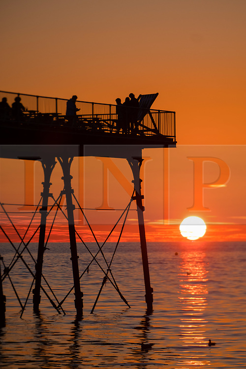 © Licenced to London News Pictures. <br /> Aberystwyth, UK. 25/7/2018.People  are silhouetted by the glorious setting sun over Aberystwyth pier at the end of a day of hot summer sunshine.  The UK wide heatwave continues, with little respite from the very dry weather  despite some rain in the forecast for the weekend. Photo credit: Keith Morris/LNP