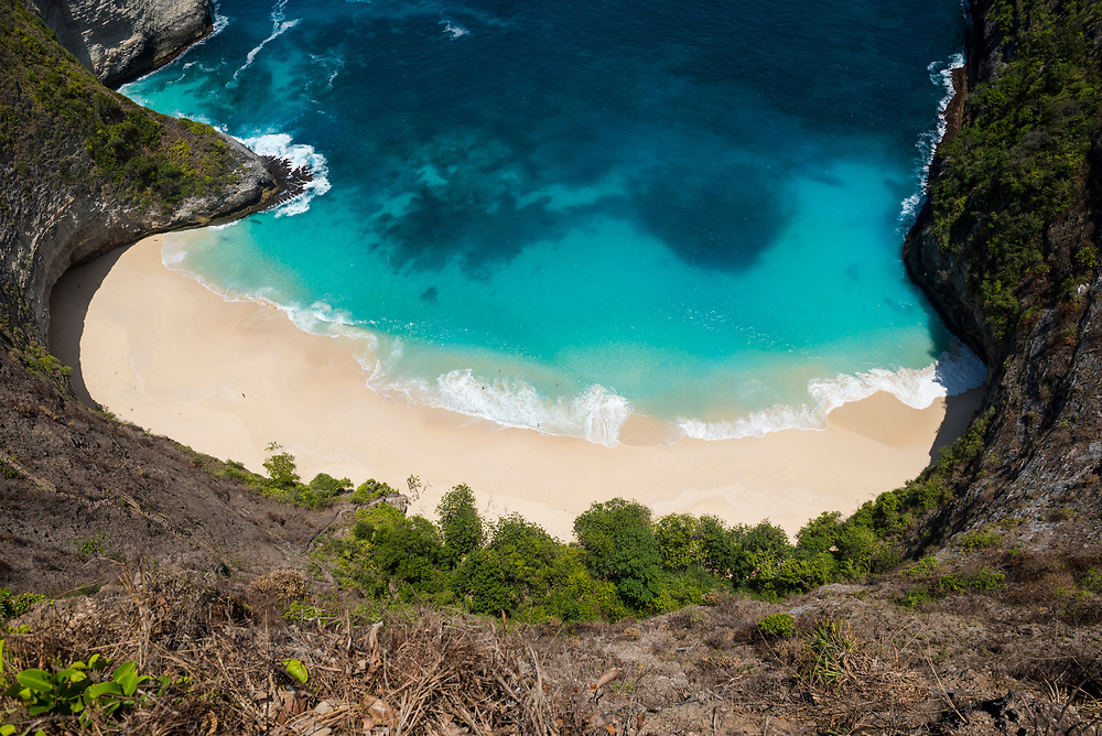 Nusa Penida, Indonesia - October 3, 2017: High angle view of Kelingking Beach, a natural landmark and tourist destination on the Indonesian island of Nusa Penida. Several people are on the beach.