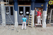 Decorators paint the pillars on the exterior of a pub in Southwark, on 26th March 2019, in London, England.
